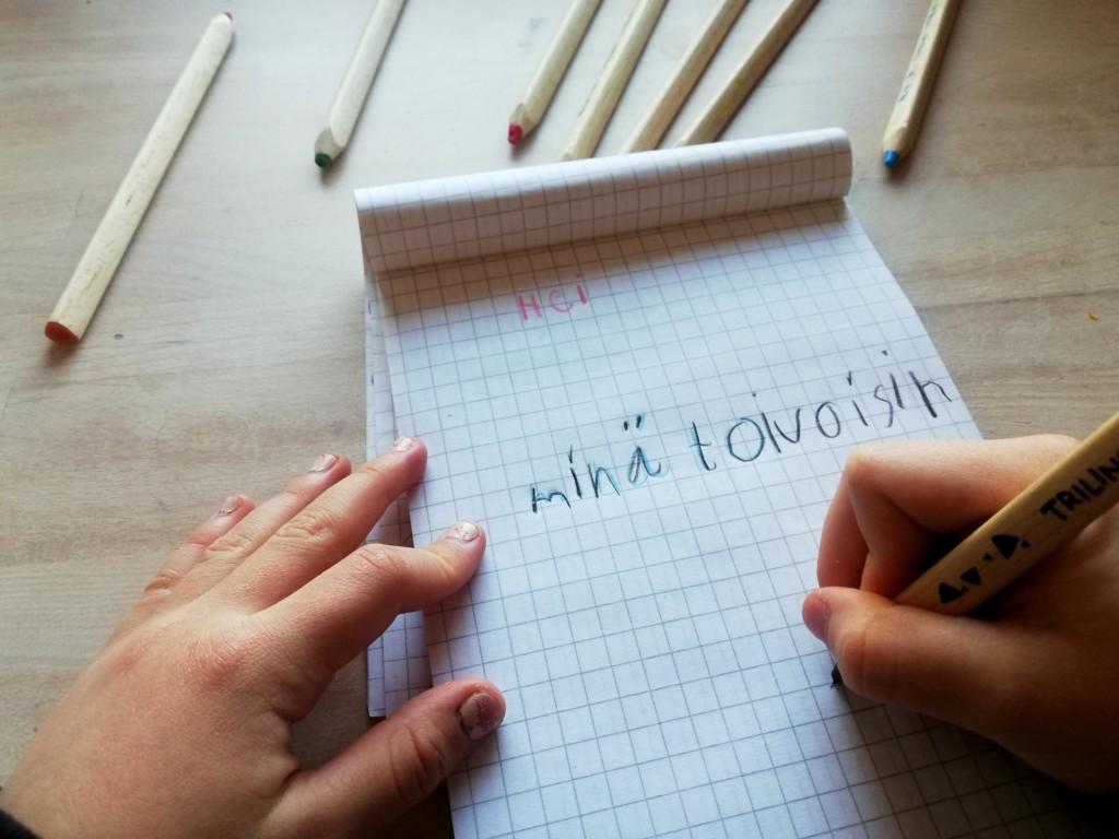 Kuvassa lapsi kirjoittaa kirjettä. Kirjeessä lukee; Hei, minä toivoisin.